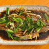fresh steamed whole fish covered with herbs onions and sauce